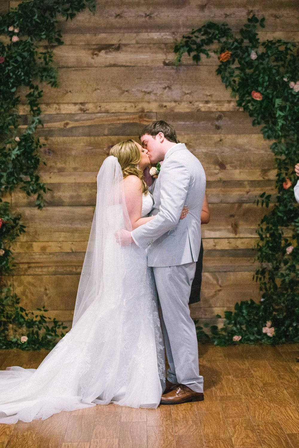 Bride and groom kissing infront of greenery archway against wood wall