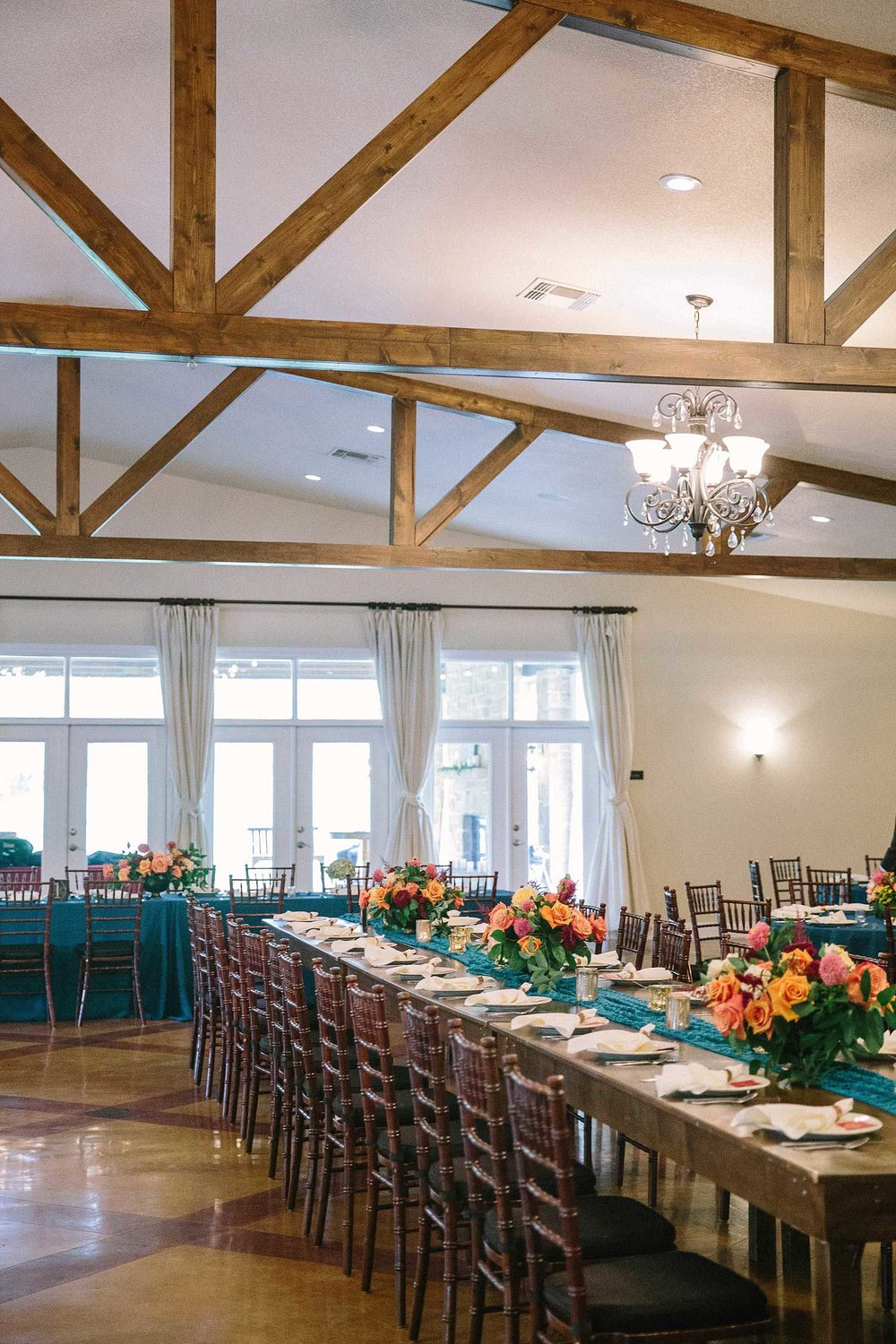 The orchard Azle TX wedding reception with blue tablecloths and a farm table