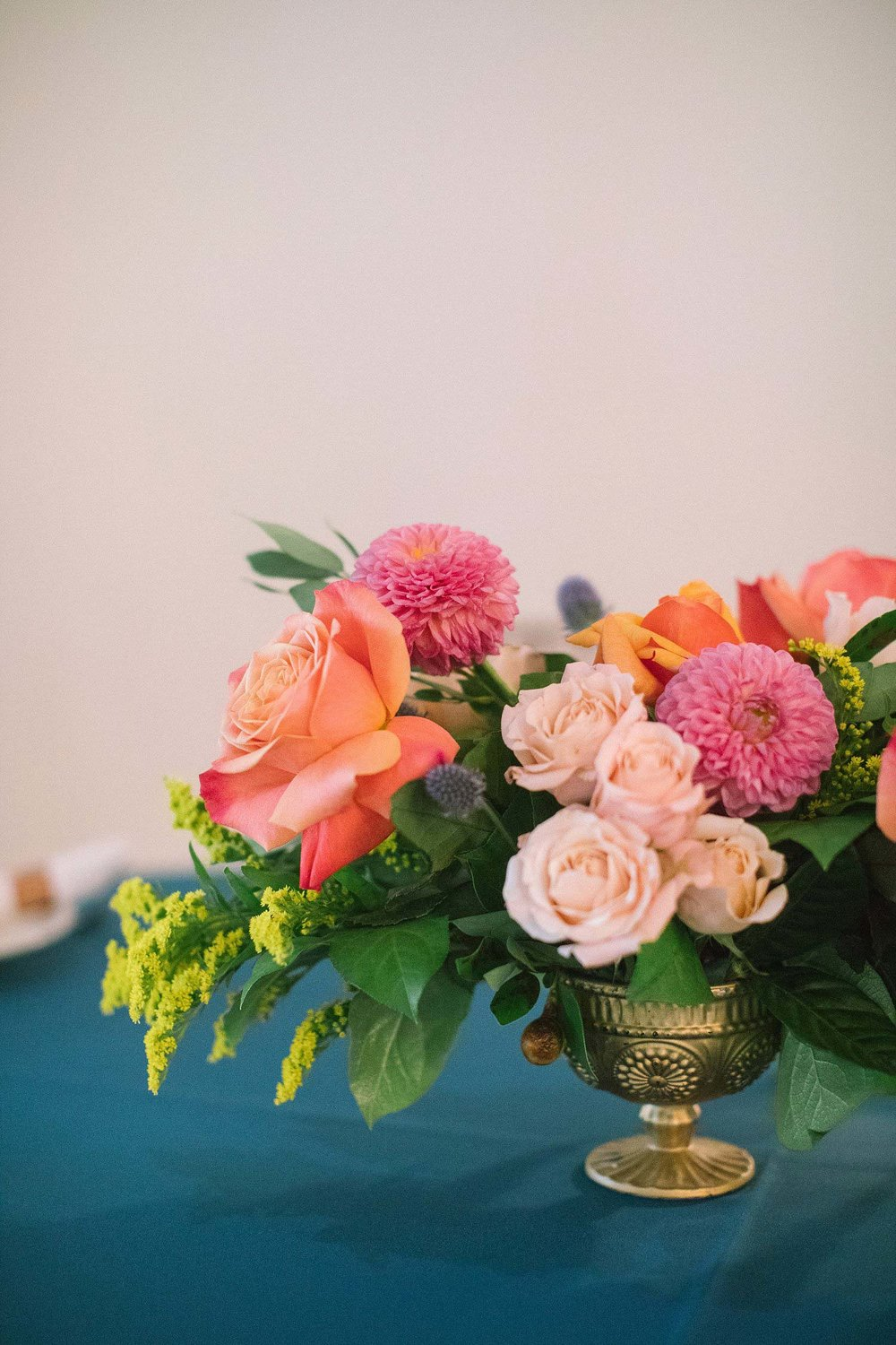 coral cream and apricot flowers with a blue tablecloth