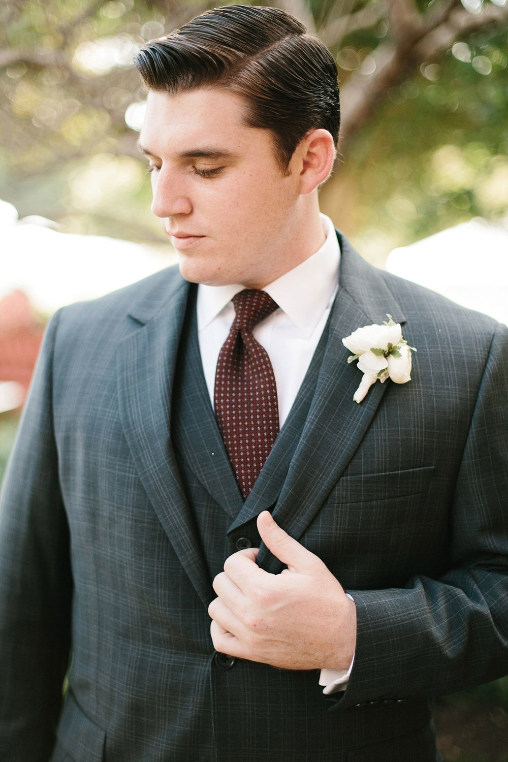 Groom in dark grey suite with vest and a burgundy tie