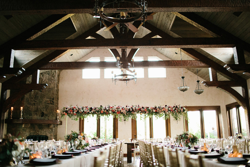 Wedding reception with large wood beams and tall floral hanging centerpiece