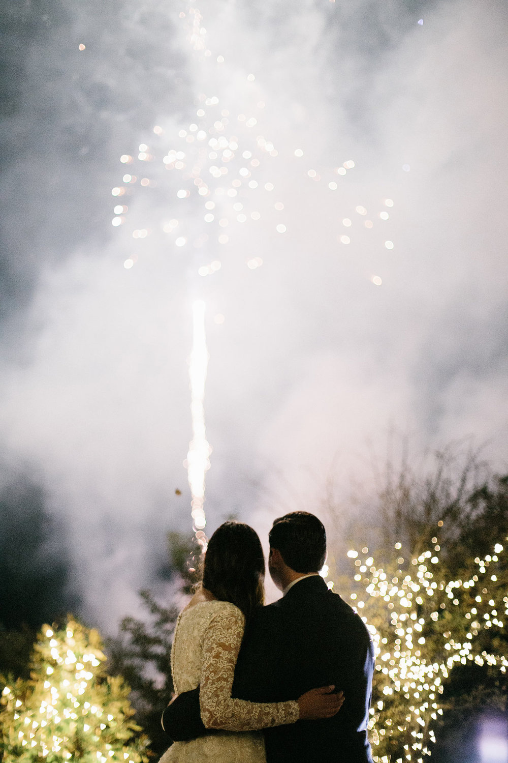 Bride and groom watching fireworks at the end of the reception