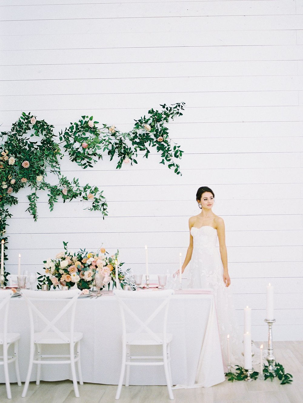White tablescape and greenery wall feature at the Nest at Ruth Farms