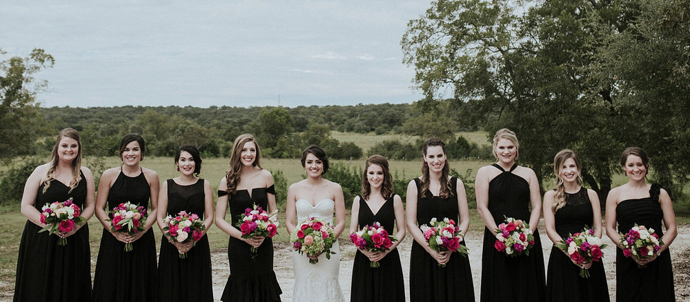 bridesmaids in long black dresses holding pink bouquets