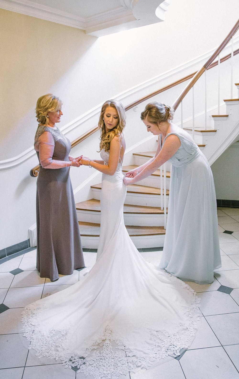 Bride and maid of honor putting on brides dress