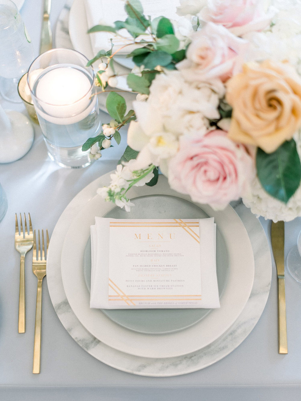 Place setting with marble charger and gold silverware
