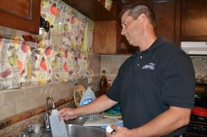 Supervising Environmental Health Specialist for Riverside County DEH Mark Abbott takes a sample from a newly installed water treatment system