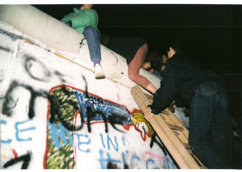 People climbing over a graffiti Berlin wall in 1989.