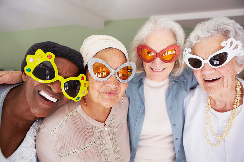 A group of women smile while wearing novelty sunglasses