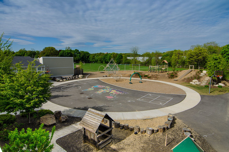 "The Lower School Playground at Shore Country Day School in Beverly, MA integrates ""natural play"" elements, an embankment slide, and remnants from a beloved prior installation."