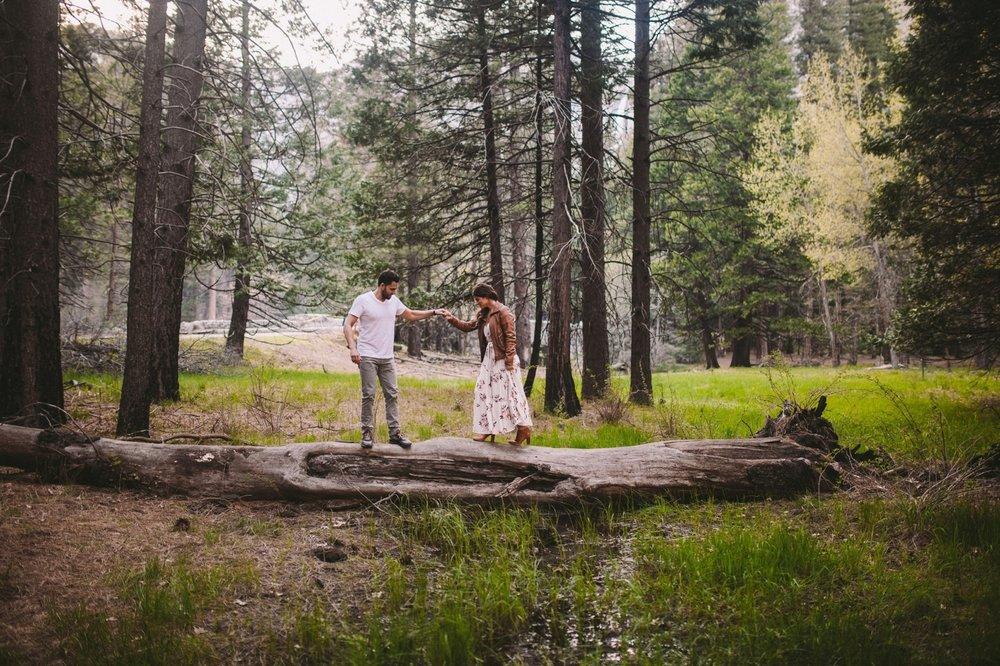 Couple Walking Over Log in Yosemite