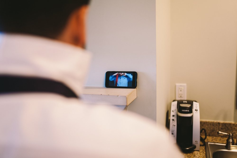 Groom Watching Youtube Video on How to Tie a Tie for Wedding