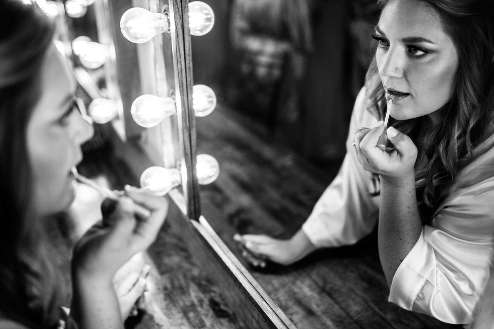 Black and White Photo of Bride Putting on Lipgloss in Mirror - Wedding Prep