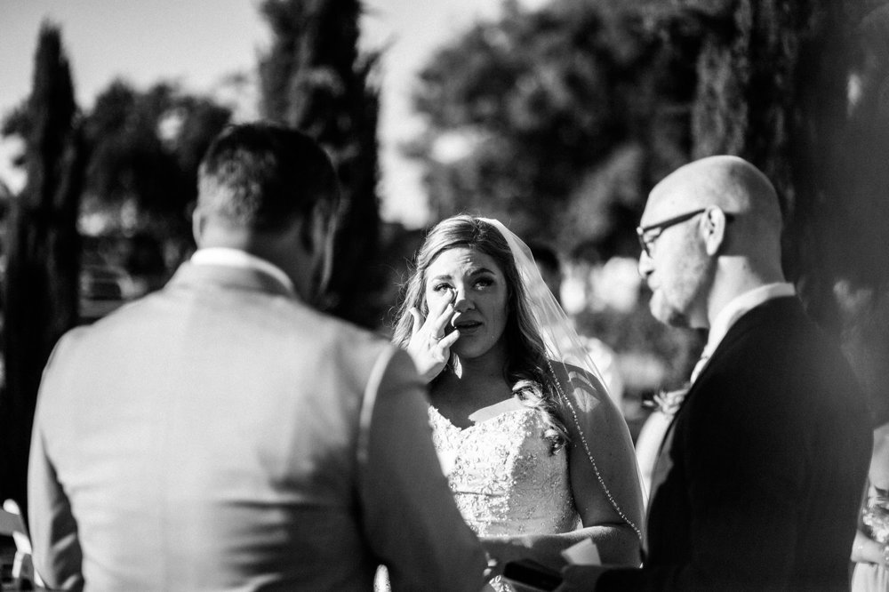 Black & White Photo of Bride Crying During Grooms Personalized Vows in Outdoor Vineyard Wedding Ceremony