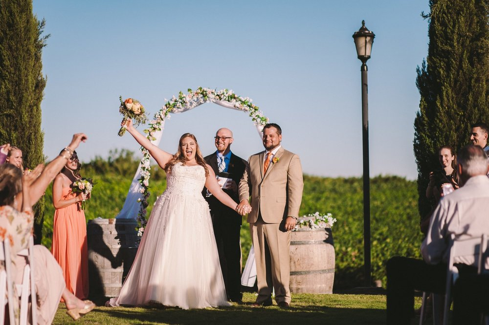 Bride Cheering with Bouquet up in the Air After Outdoor Wedding Ceremony