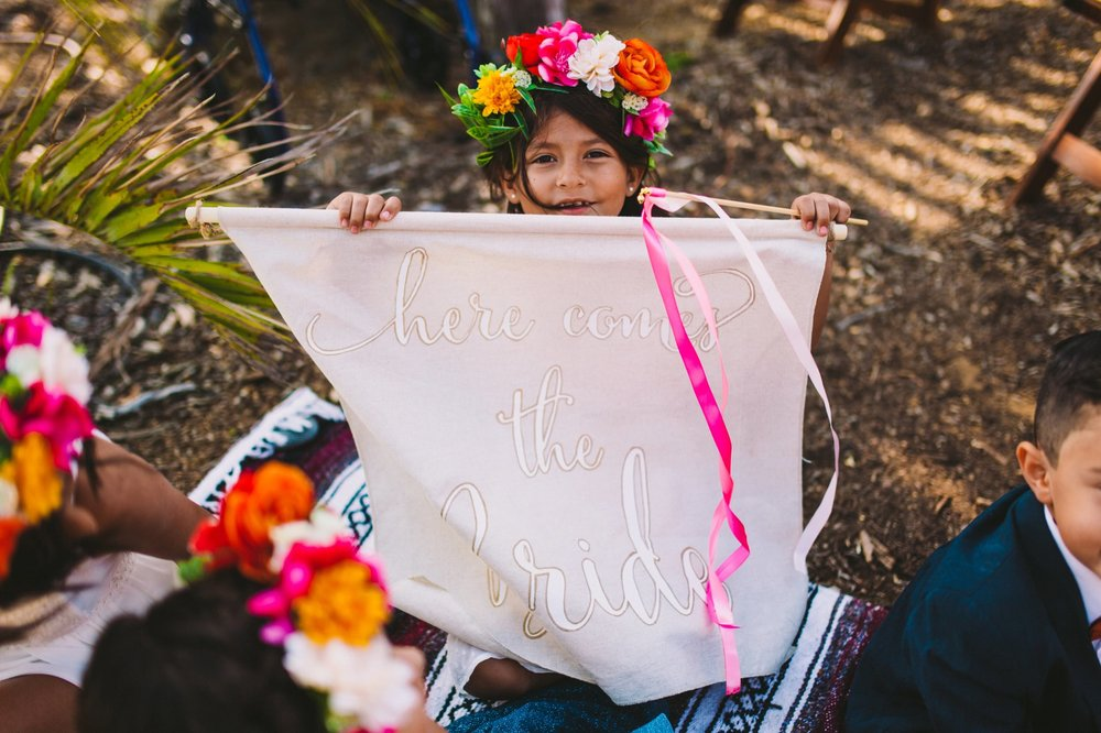 Colorful Flower Crown & Flower Girl Holding 'Here Comes the Bride' Banner