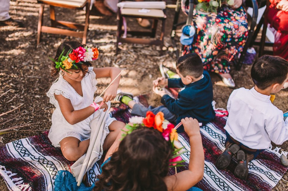 Flower Girls & Boys Watch Ceremony From Colorful Blanket Next to Wedding Arch