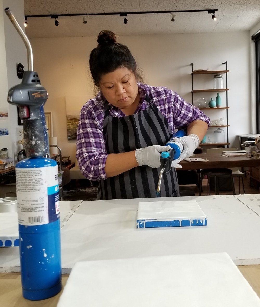 Throwing fire with blow torches to turn encaustic to a fluid, malleable state.