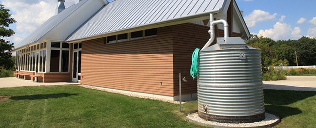 Rainwater catchment with steel roof and tank.
