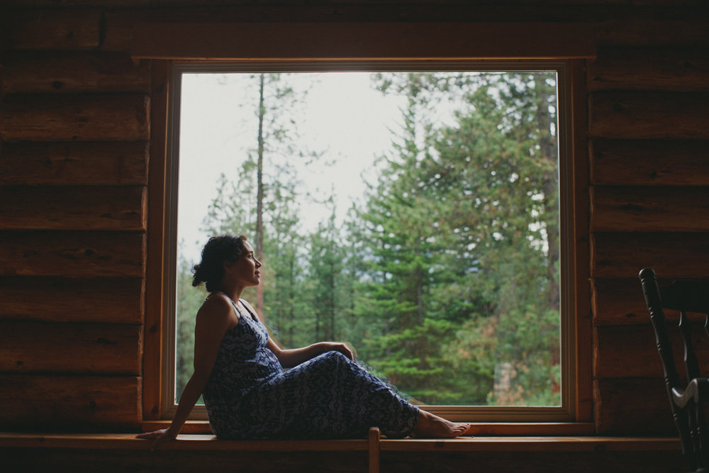 pregnant woman sitting in cabin window seat