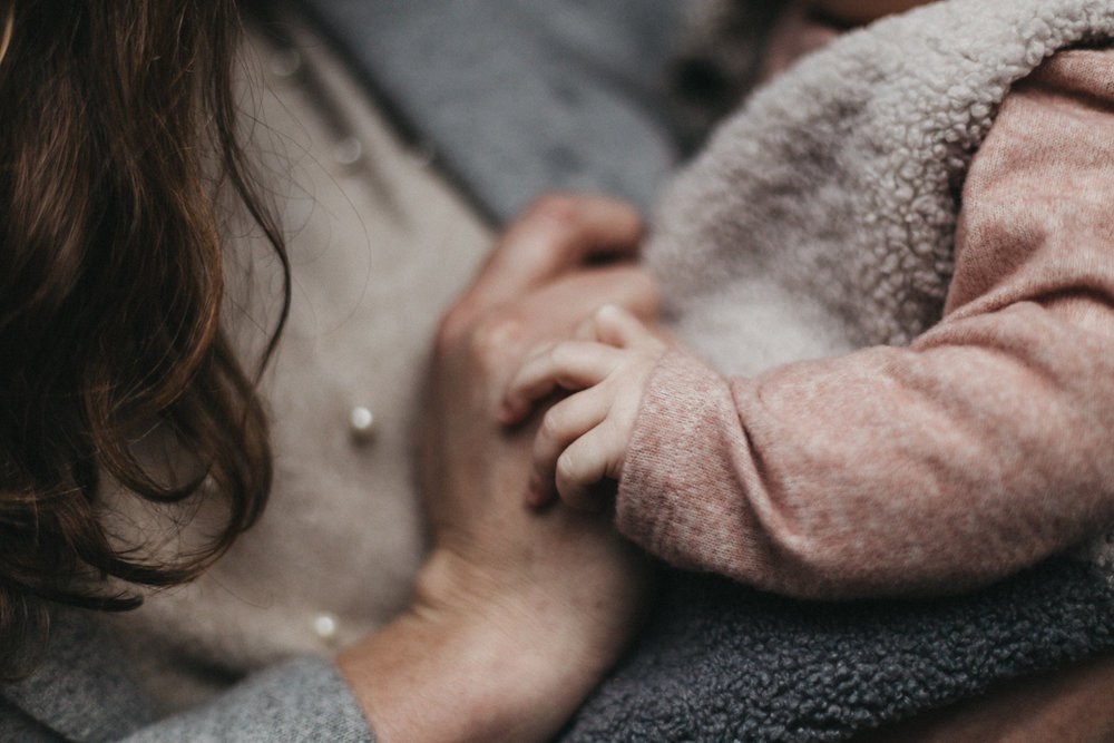 mom holding baby's hand in soft fabrics winter portrait session at pike place market
