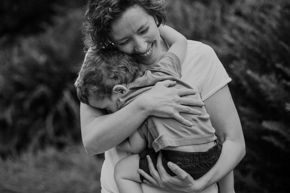 black-and-white-mother-smiling-and-embracing-her-toddler