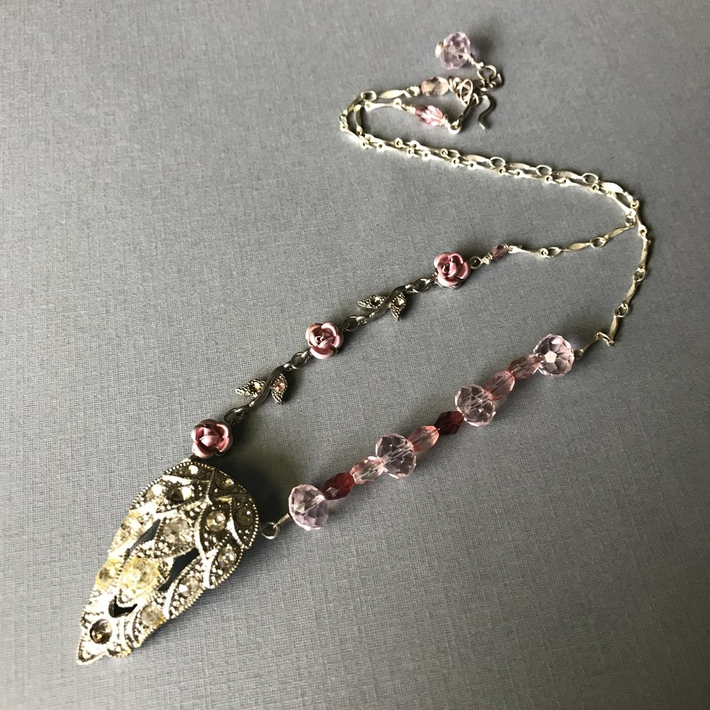 A slightly shabby 1940s rhinestone shoe clip is now the focal point of this necklace. Also using part of a 1960s rose necklace, new glass beads and silver tone chain and clasp.