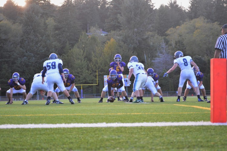 Sophomore center Aidan Adams snaps the ball to sophomore quarterback Jordan Miles.