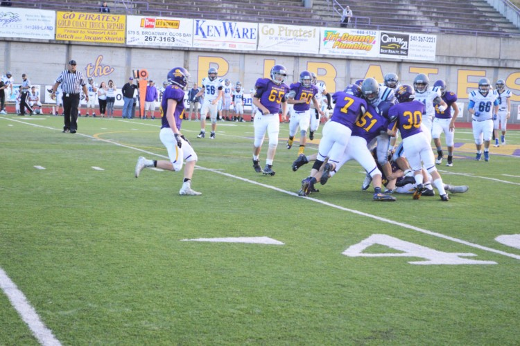 The Pirates have a collaborative effort as they tackle the ball carrier.