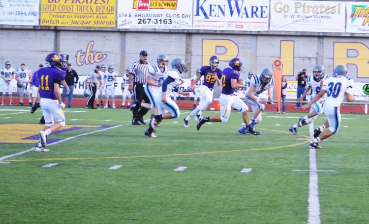 Sophomore Kaleb Hughes runs the ball for a gain of yards.
