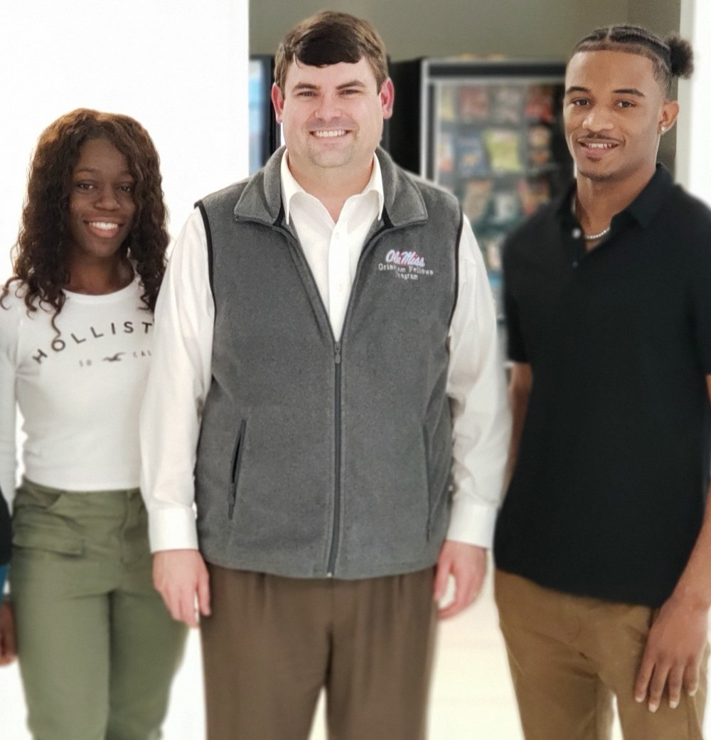 Lobaki team members Shalin Jewett (left) and Deuntay Williams (right) with J.R. Love (center) from the McLean Institute at the University of Mississippi.