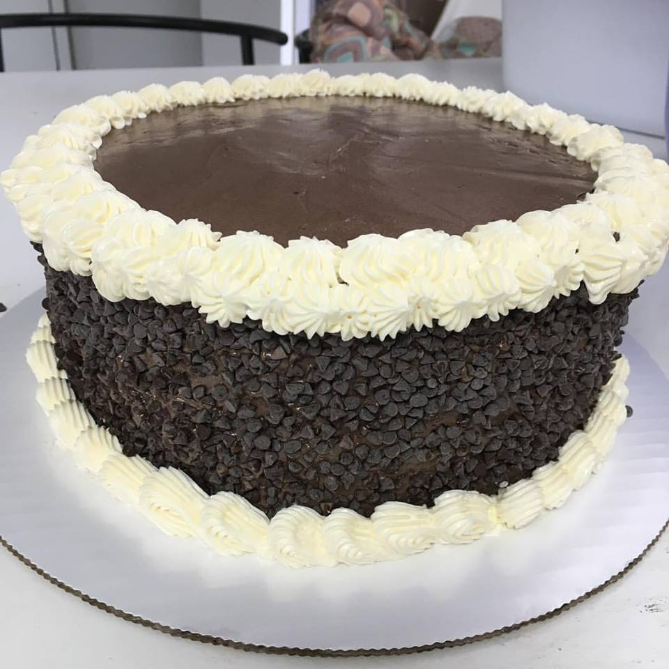Decadent chocolate cake with chocolate chips around the side and white icing on the edges