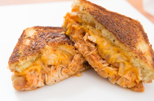 Los Pollos - Buffalo style pulled chicken with cheddar cheese, sauteed onion, pickle and ranch on basil buttered grilled texas toast.