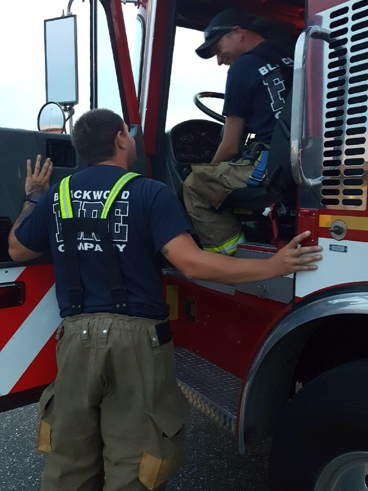 Firefighter Lemmerman conversing with Firefighter Fulcher (Driver in Training)