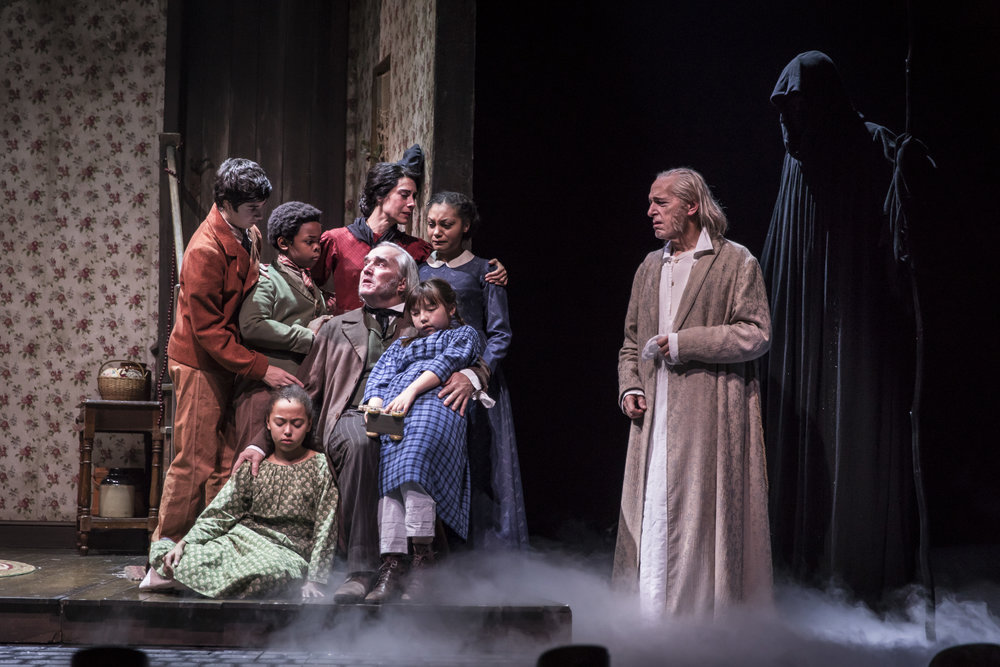 Aaron Stone  (Peter Cratchit),  Kei  (Kei Cratchit),  Andrea Crisp  (Belinda Cratchit),  Michele Vasquez  (Mrs. Cratchit),  Ron E. Rains  (Bob Cratchit),  Ariana Burks  (Martha Cratchit),  Maggie Chong  (Emily Cratchit),  Larry Yando  (Ebenezer Scrooge) and  Breon Arzell  (Ghost of Christmas Future)   in the 40th annual production of  A Christmas Carol , directed by Henry Wishcamper.