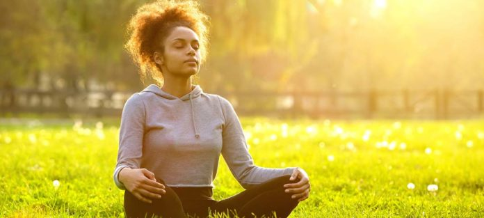 young-african-american-woman-meditating-in-nature-iStock-478811176-rev-696x313.jpg