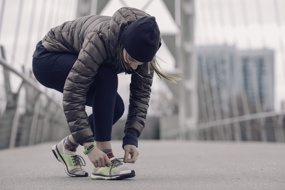 woman runner tying shoes able to run from physical therapy athletity