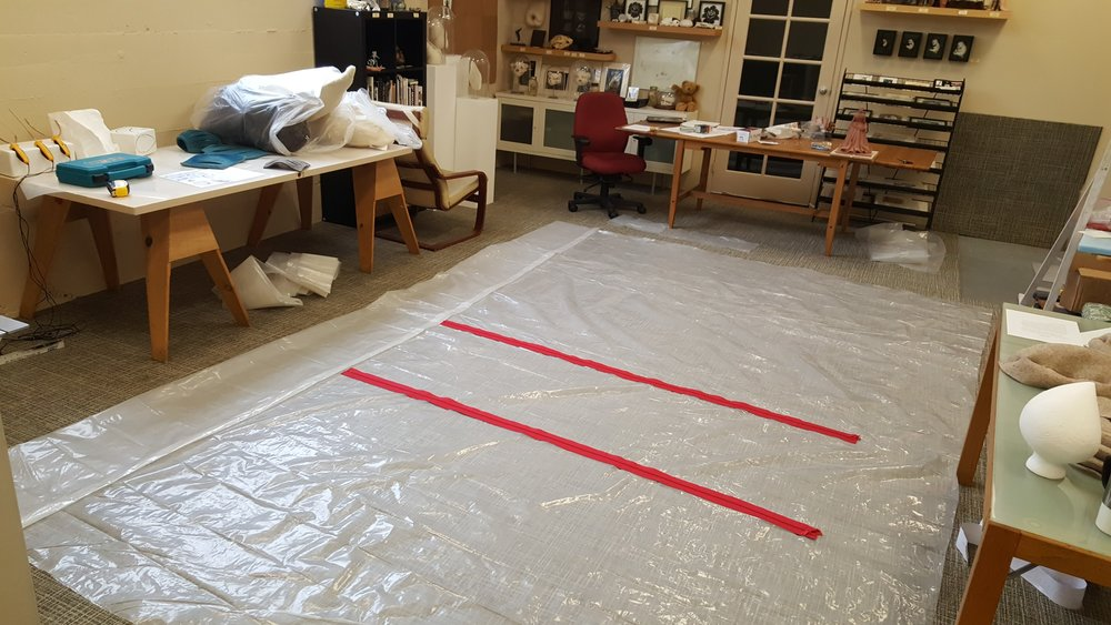 Laying out plastic on the blessedly large floor in order to stick on the zipper door kit-- basically two long zippers with sticky sides you can apply to the plastic, then cut in the center.