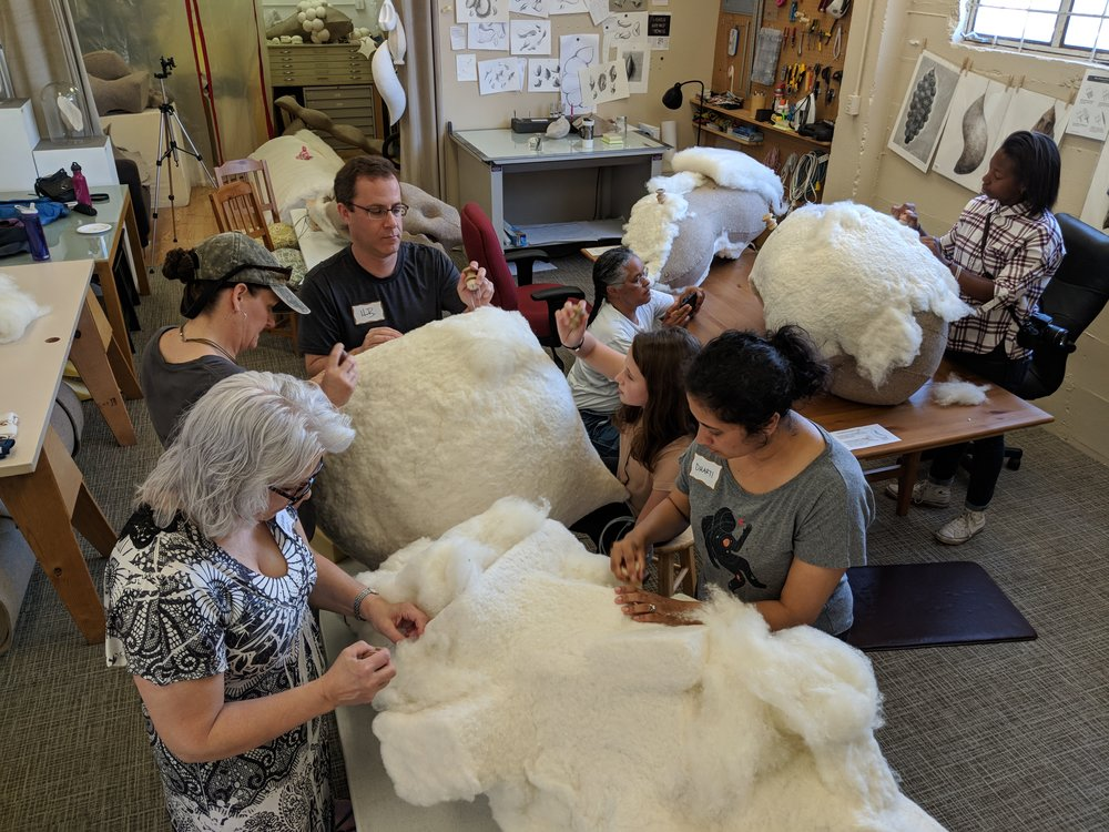 Volunteers helping apply wool to cover the 'Hanging Pod' forms at a Felting Party using felting needles. Serious faces reflect how absorbing the activity can be; interesting conversations and laughter abounded as well!