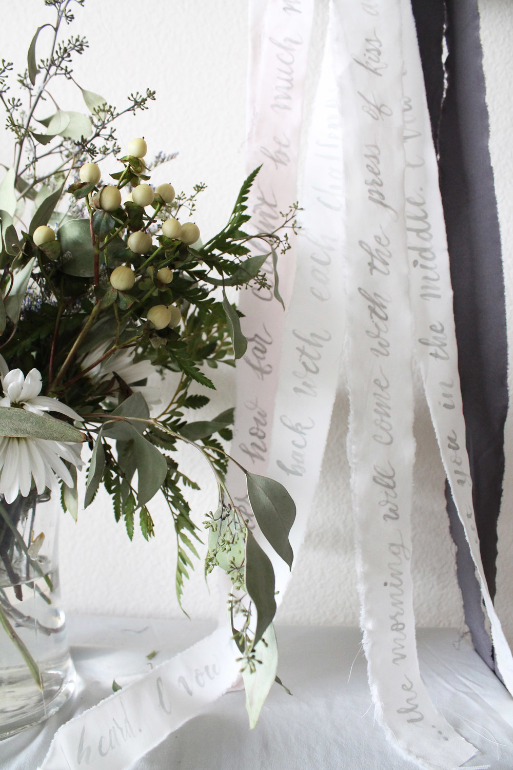 bouquet ribbon calligraphy for wedding day details. written song lyrics in calligraphy for bouquet