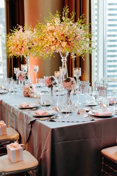 55. Trump Tower. Pen Carlson Photography. Sweetchic Events. Vale of Enna. Head Table . Gray Linens. Glass Vase topped with an array of pink and white dendrobium orchids.