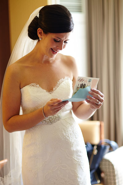 12. River East Art Center Wedding. Dennis Lee Photography. Sweetchic Events. Bride reading card from groom.