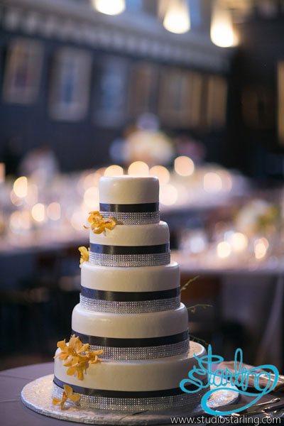 30. U of C Hutchinson Commons Wedding. Studio Starling. Sweetchic Events.White Tiered Cake from Continental Bakery with Black Ribbon, Rhinestones, and Yellow Orchid Accent