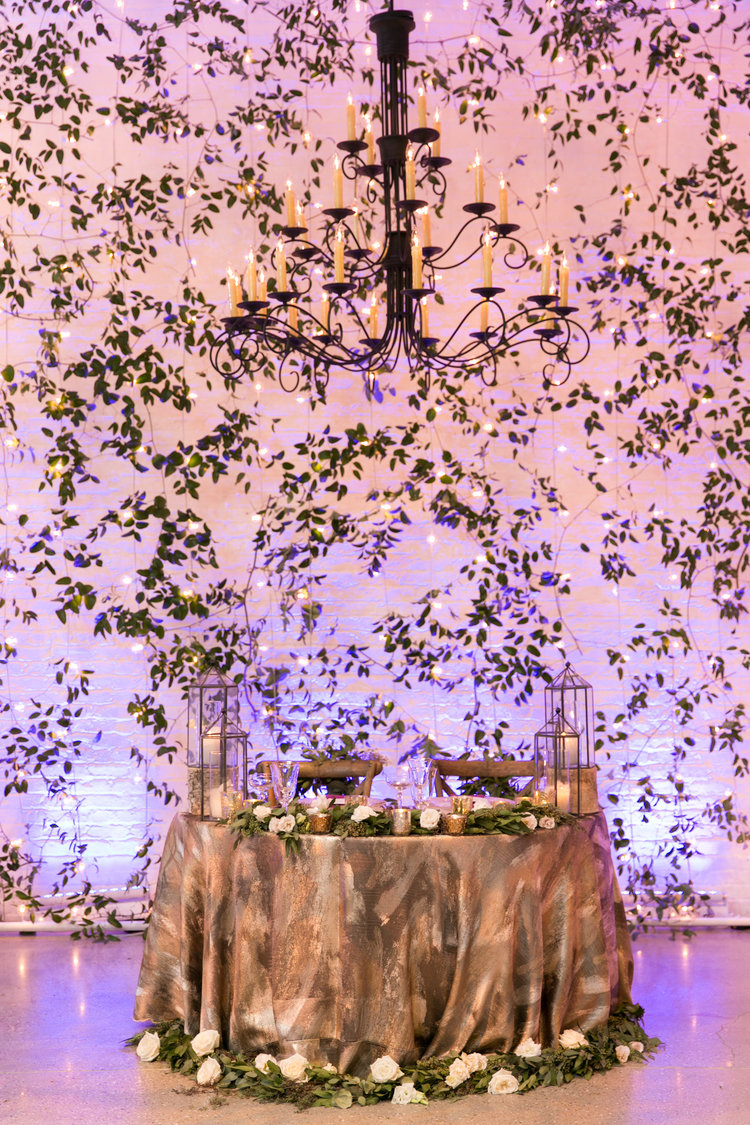 Dramatic sweetheart table with gold linens, candles, and trailing greenery