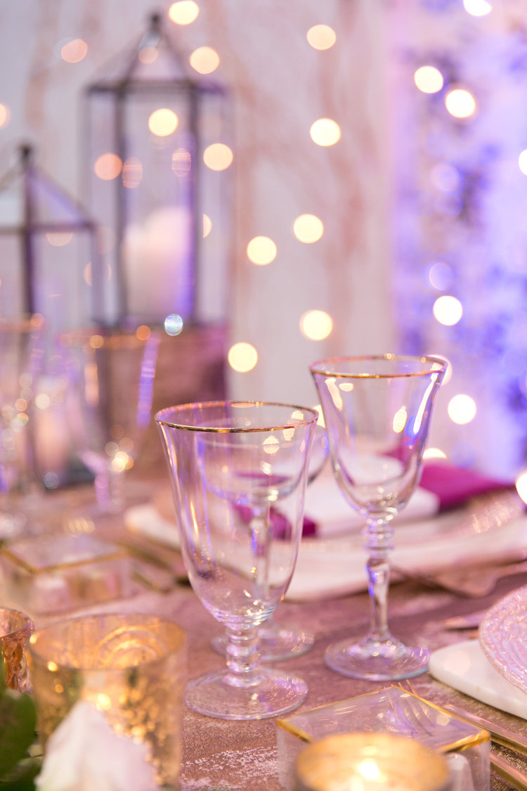 sweetheart table with gold, greenery and lanterns
