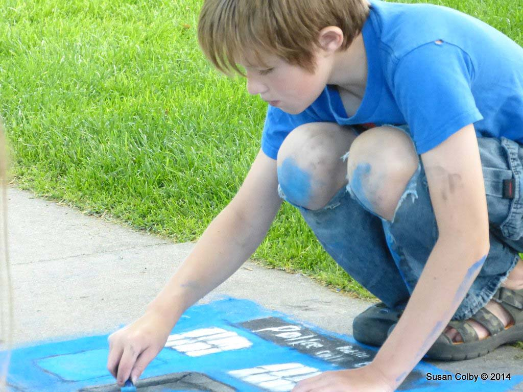 Great concentration and full body participation in the sidewalk art competition