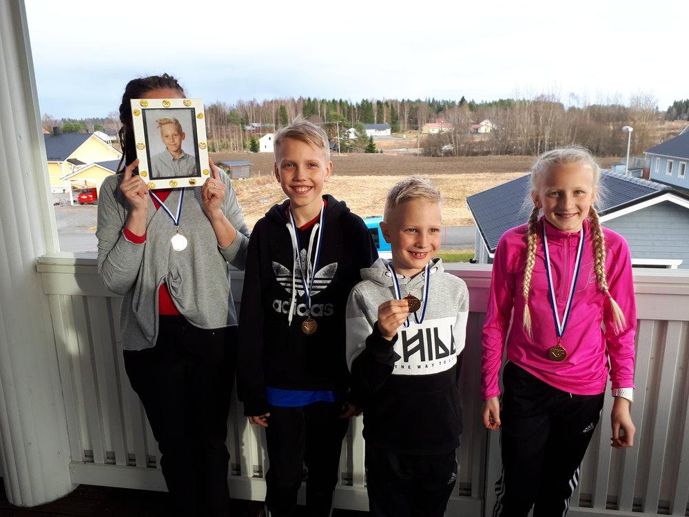 """Kultamitalikahvittelun lomassa otettussa kuvassa tuoreet piirinmestarit """"Vikki"""", Veikka, Väinö ja Lotta."""