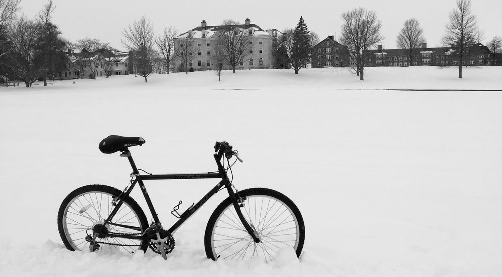 Bicycle in the snow with college buildings in teh background. Links to Blog Page.