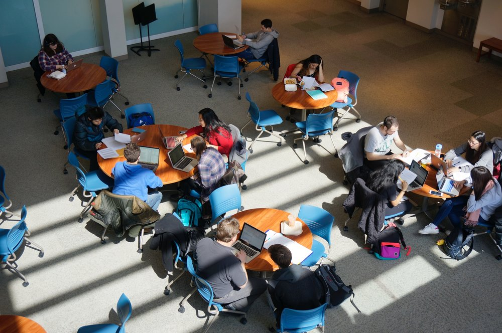 COLLEGE STUDENTS STUDYING AT TABLES IN A STUDENT UNION. LINKS TO THE BLOG PAGE OF THIS SITE.