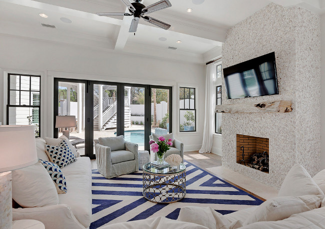 The fireplace is Tabby Shell Stucco, brings the seaside indoors, and the white-slip covered furniture accented by navy blue is perfect color-scheme for a coastal beach house. The blue and white striped rug is from Serena Lily.